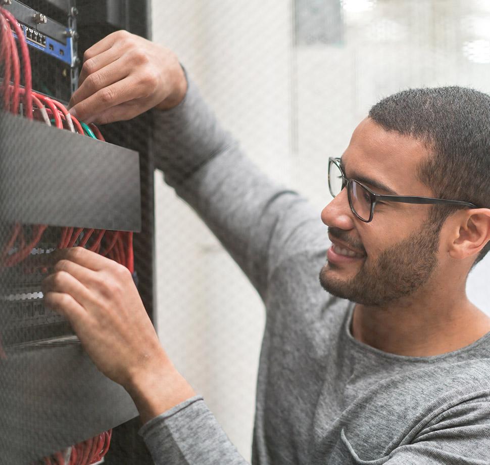 DSL vs. Kabel-Internet: Die Unterschiede. Das Artikelbild zeigt einen Techniker beim Anschluss von Kabeln an einen Server.